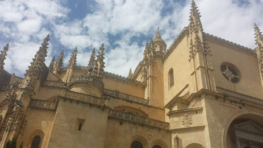 The tanned Catedral de Segovia shot from below, with views of the blue sky and clouds