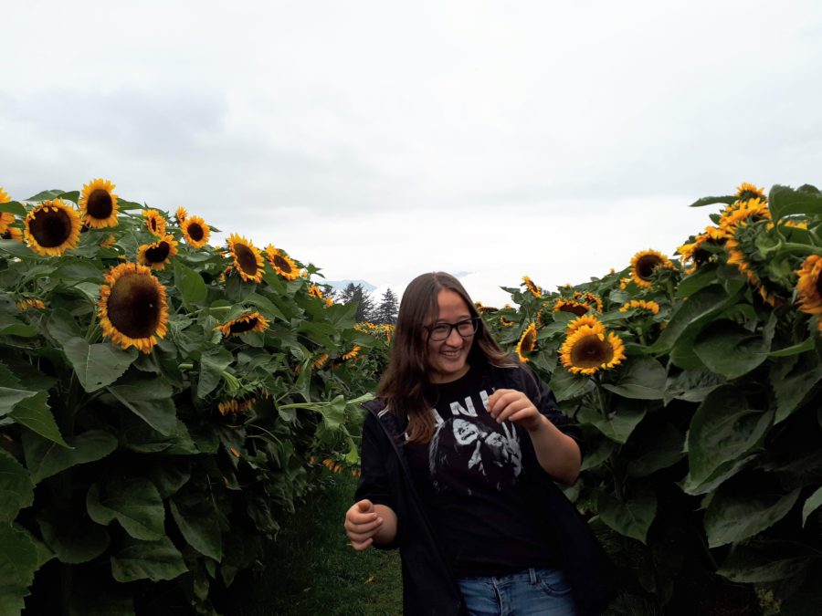 Mia laughing in front of sunflowers at festival
