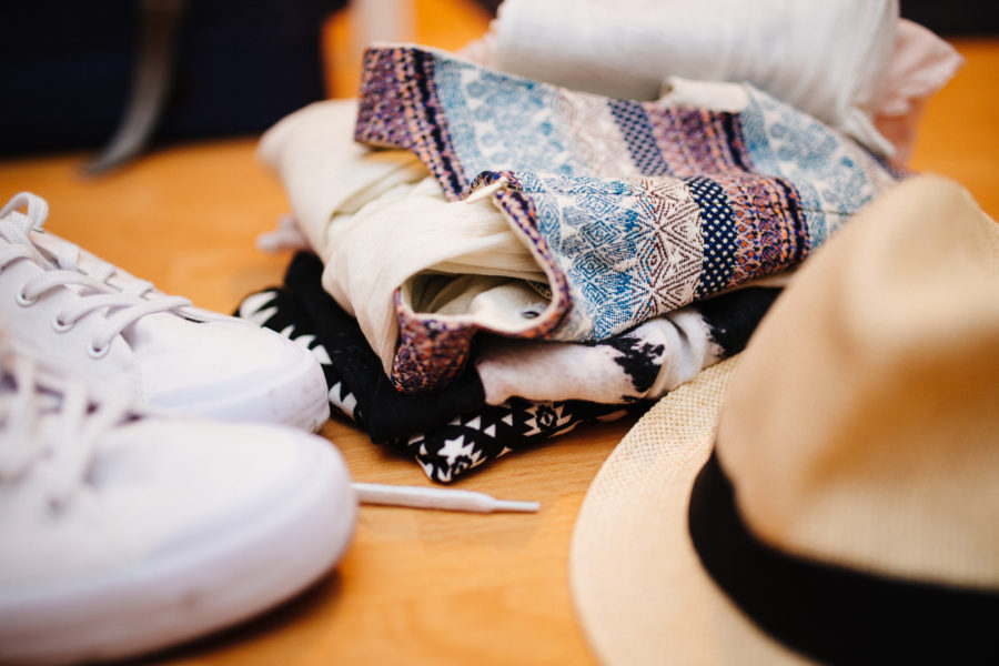 Fedora hat beside white sneakers and folded clothes.