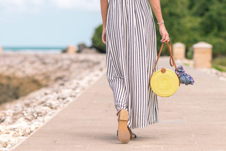 Woman wearing striped long maxi skirt holding brown bag by the beach.