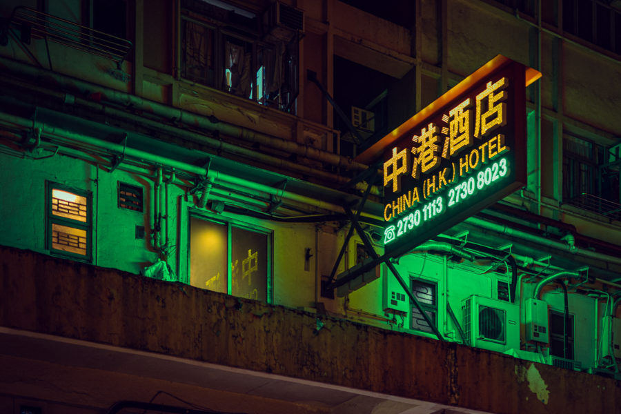 """Sign of """"China (H.K.) Hotel"""" at night, with green lighting"""