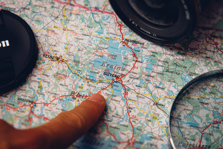 Finger Pointing Gizycko on Country Map with Cameras