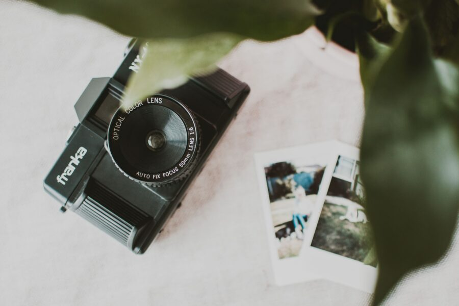 Black mirrorless camera on white counter with fern and pictures