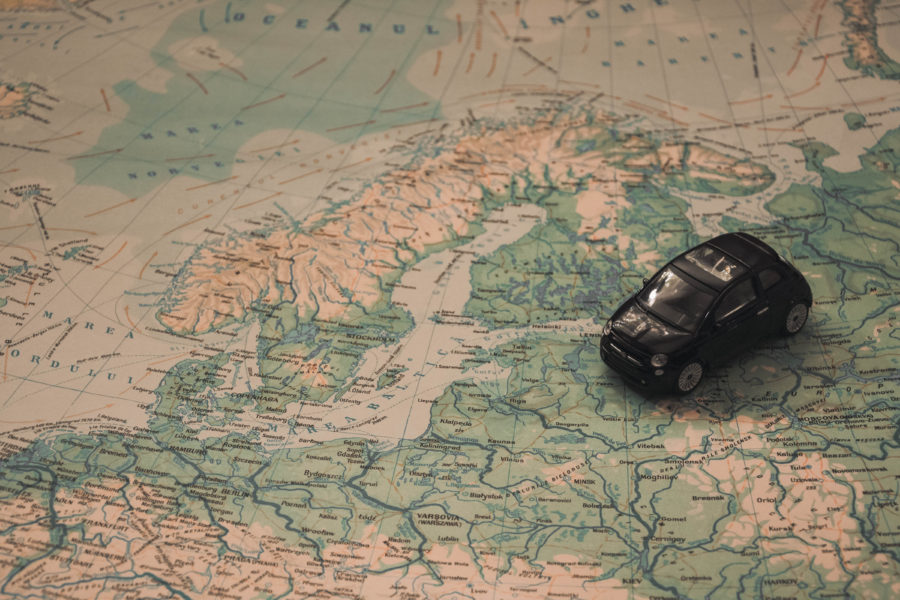 Black toy car on map of Europe