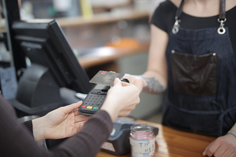Women tapping a credit card at a counter