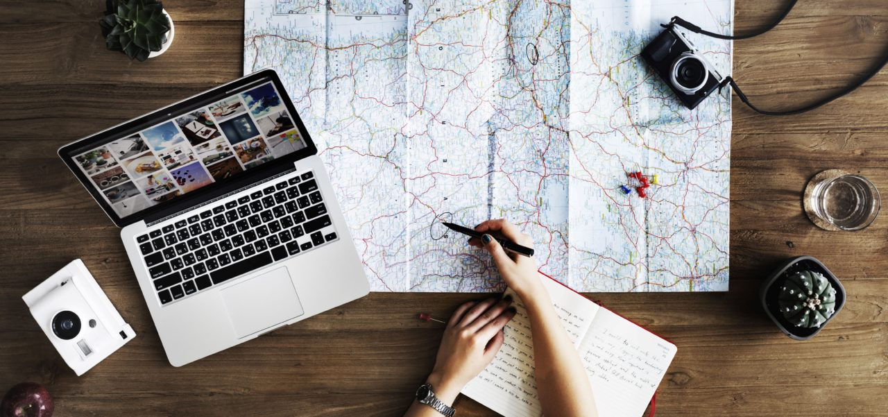 Person planning a trip with a map, laptop, camera, and notebook