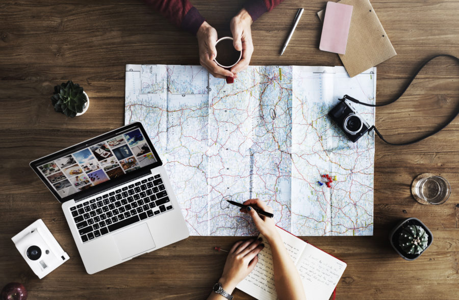 Two people planning a trip on a map, with a laptop, notebook, coffee, and cameras.