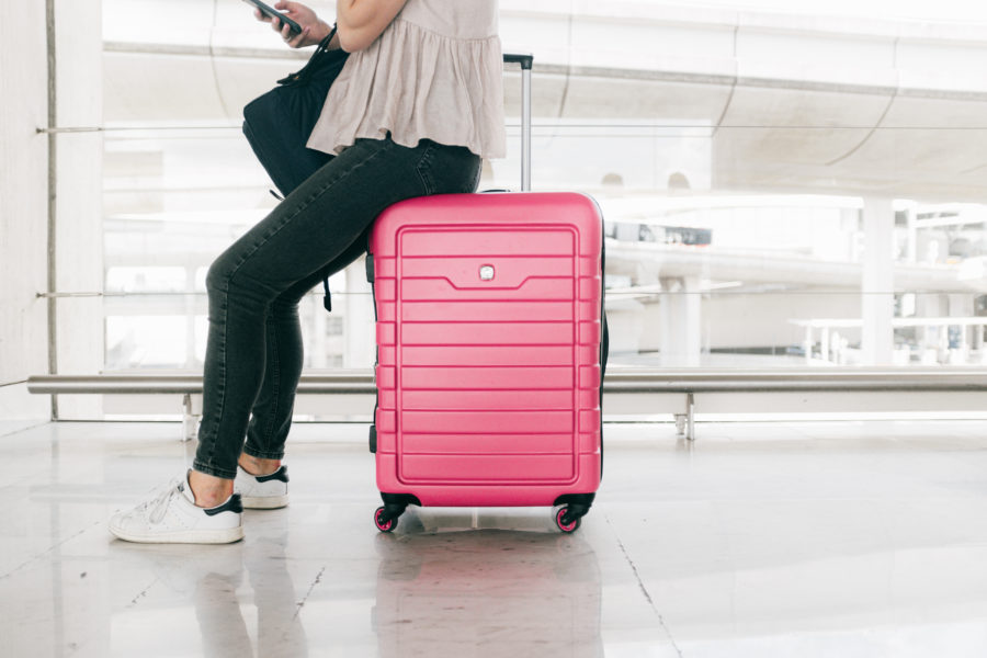 Woman sitting on a pink suitcase in an airport