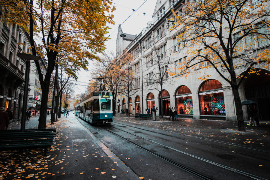 Train on street in Europe, surrounded by trees with colorful, fall leaves