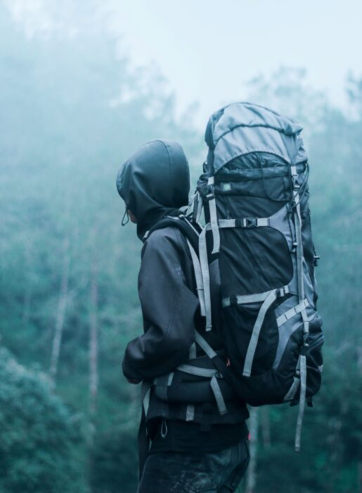 Person holding large, black, hiking backpack in misty forest