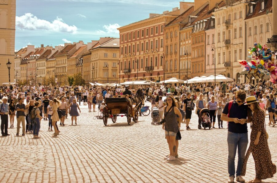 Large crowd of tourists exploring Warsaw in the sun