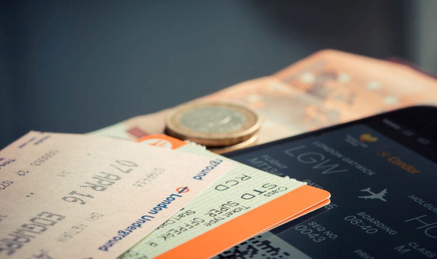 Airplane tickets, spare change, and flight info on phone