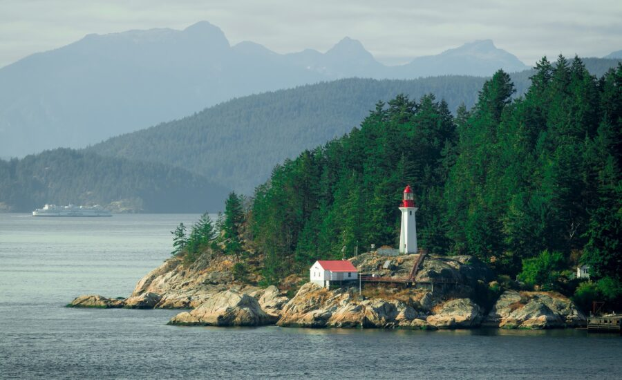 A view from the ocean of the lighthouse at Lighthouse Park, Vancouver, surrounded by mountains