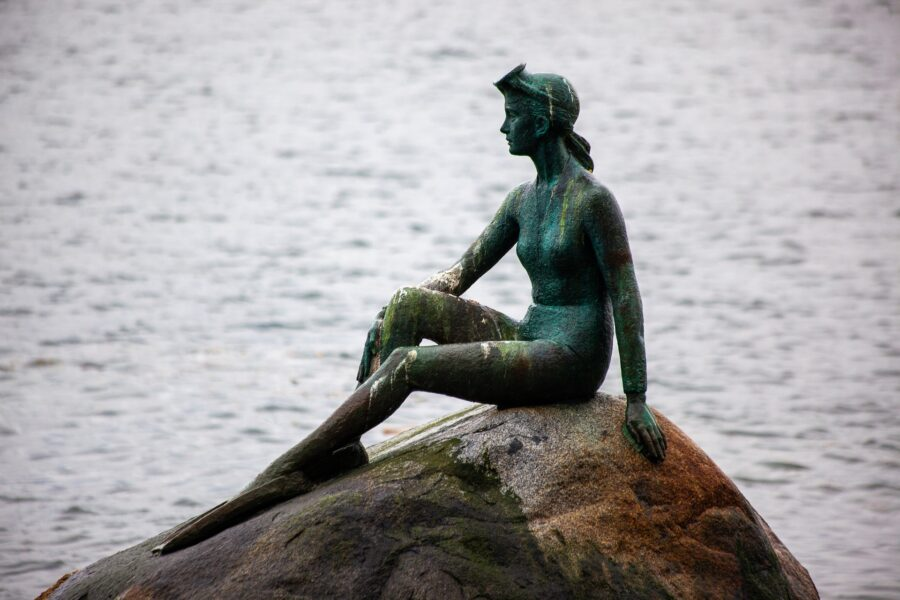 A statue of a woman on a rock in the ocean, visible from the Vancouver Seawall in Stanley Park