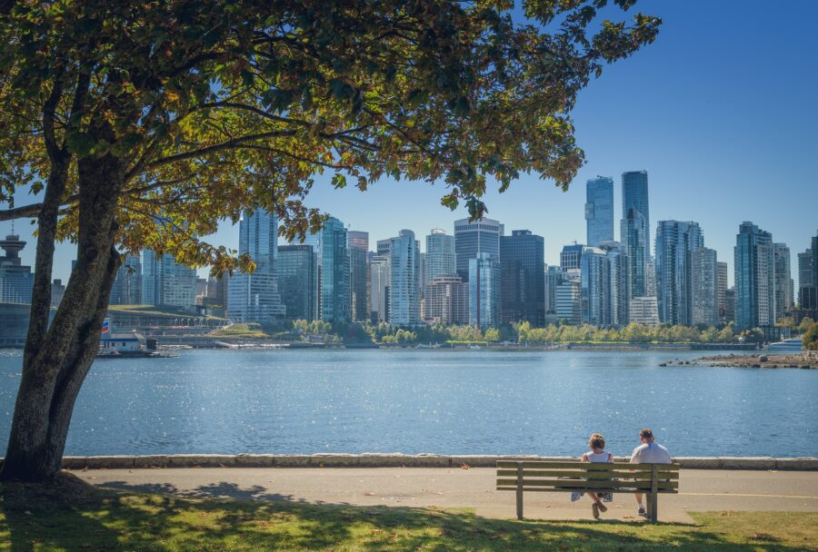 A view of the Vancouver skyline from the Vancouver Seawall, with a couple on a bench and the ocean, one of the best Vancouver walking trails