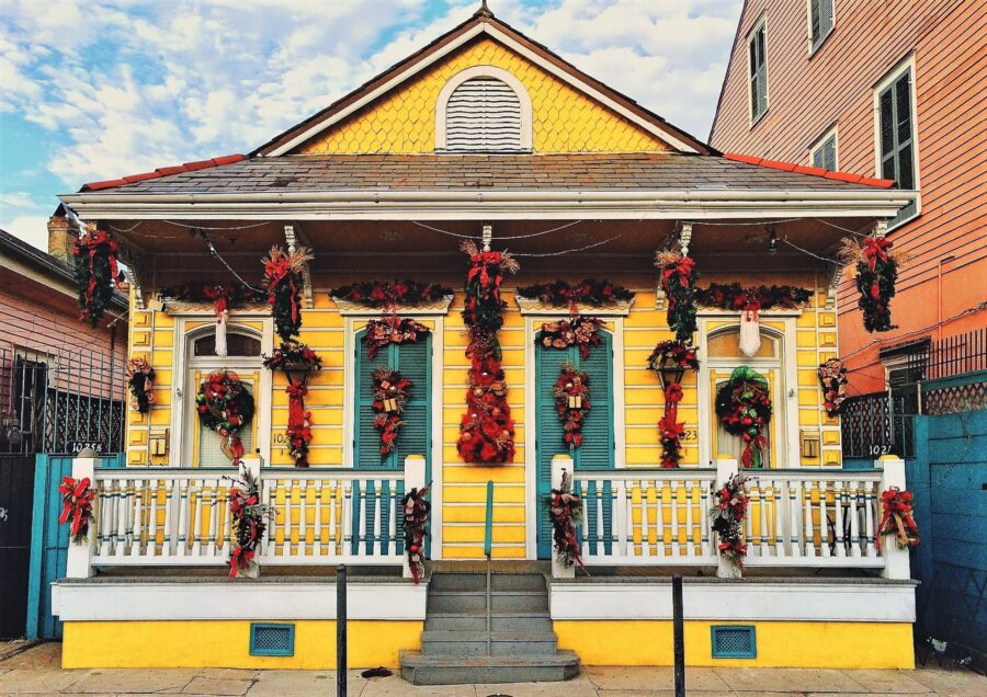 A yellow and red New Orleans house covered with decorations: one of the stops on your 3-day itinerary for New Orleans