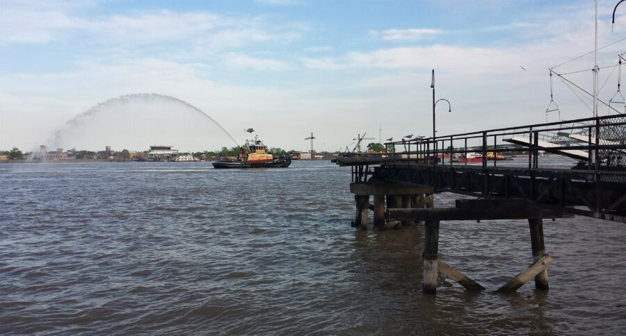 A port in New Orleans, overlooking the Mississippi River and a boat spitting out water, near the New Orleans beaches