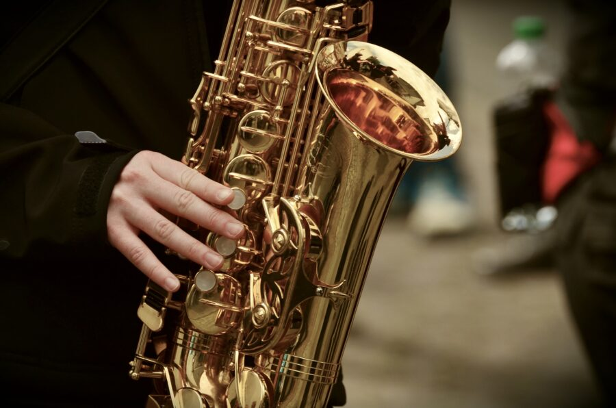 The bottom half of a saxophone and a hand playing jazz - one of the things you have to do on your itinerary for New Orleans