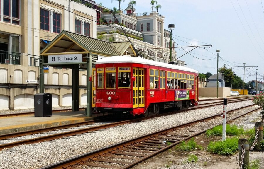 A vivid red streetcar in New Orleans at Toulouse Station, with the New Orleans architecture in the background