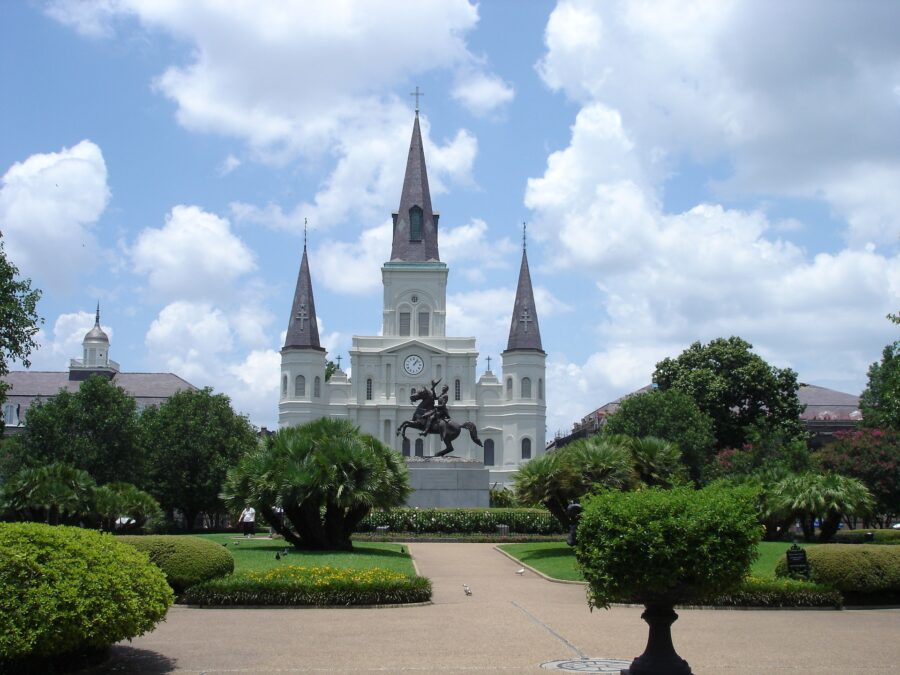 An empty Jackson Square filled with green plants and overlooking the St. Louis Cathedral in the New Orleans French Quarter