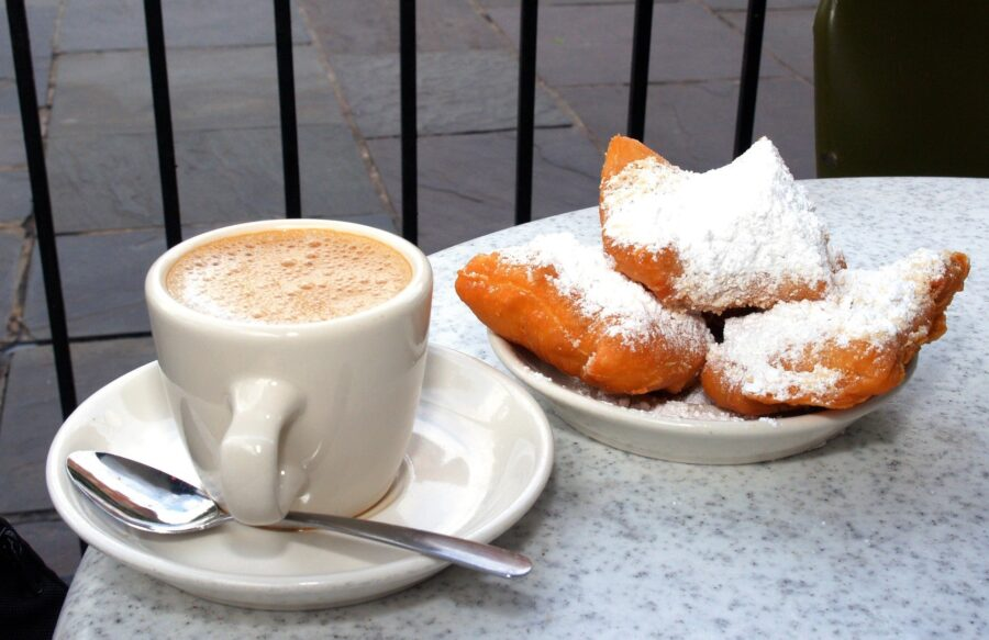 Three beignets and a coffee on a table at Cafe du Monde, an essential stop on your itinerary for New Orleans