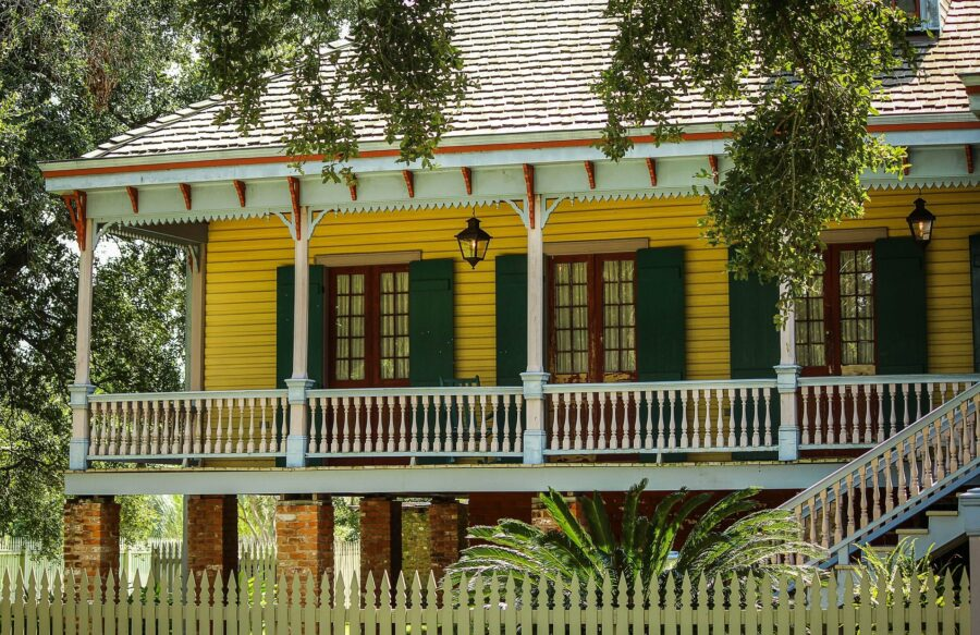 The corner of the Laura Plantation, a yellow house surrounded by greenery - one of the essential day trips from New Orleans