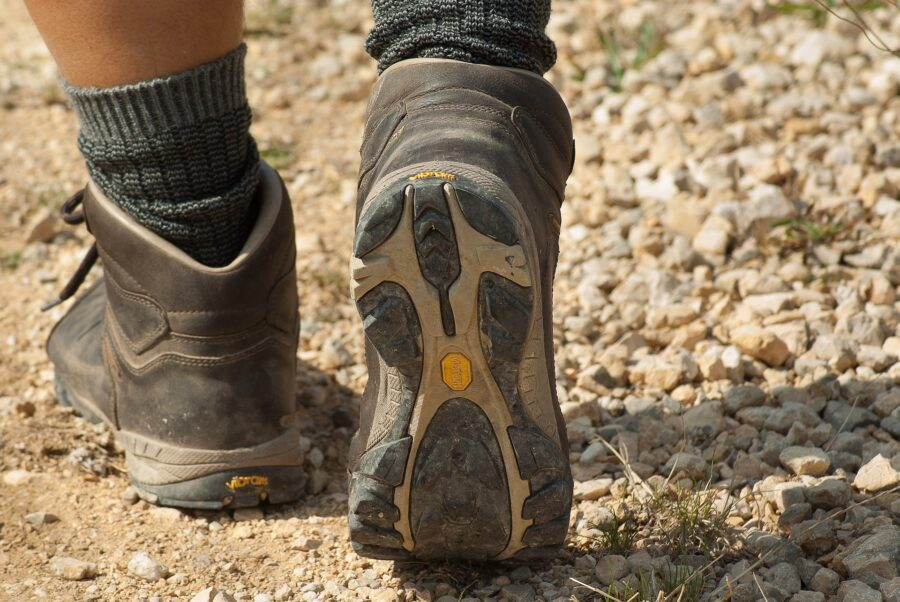 A beginner hiker's hiking boots and wool socks, walking on a dusty, rocky trail