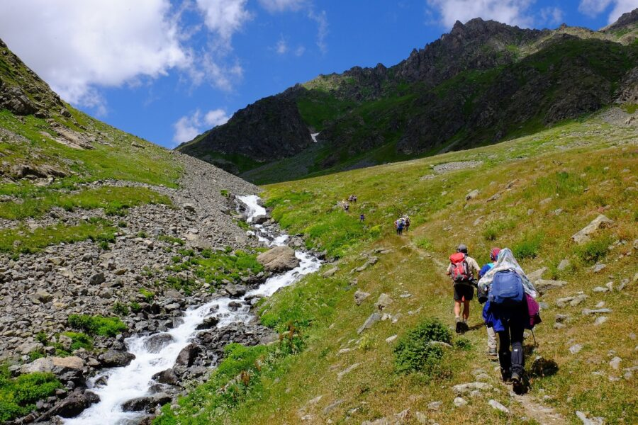 A group of hikers climbing up a mountain beside a stream in the appropriate hiking clothes, one of the beginner hiking tips to remember