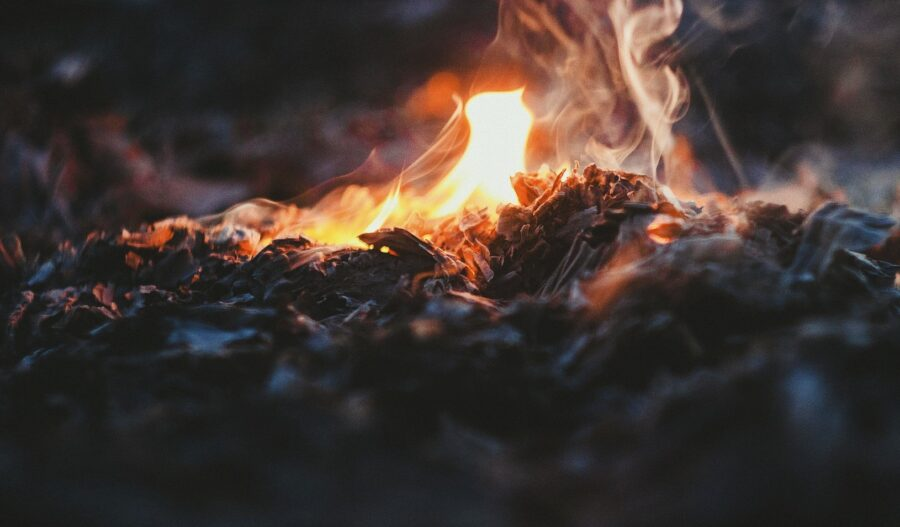 A small fire being made on the ground, one of the ten essential systems to pack for a hike!