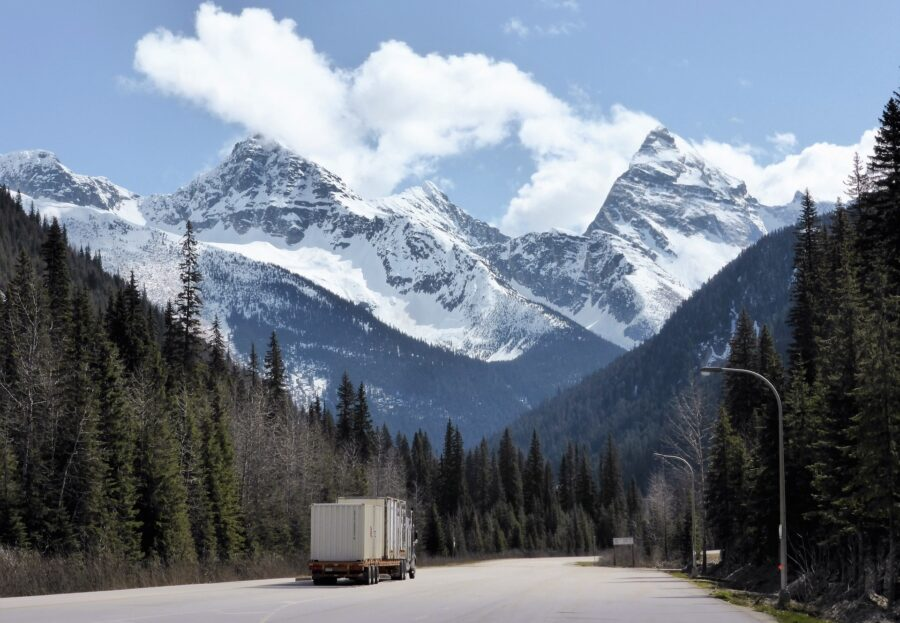 A truck driving on the Trans-Canada highway on the Calgary to Vancouver drive, with the Canadian Rockies