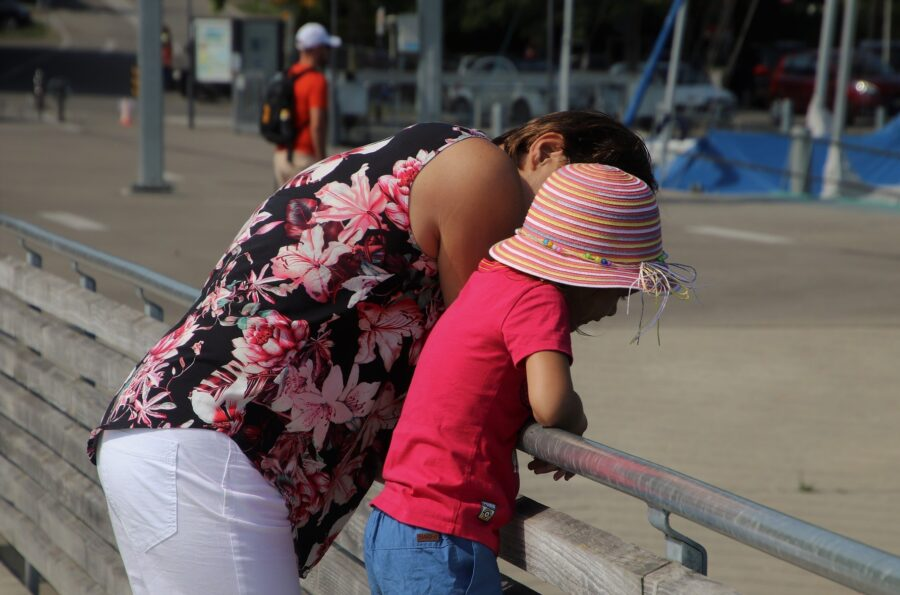 An Au Pair taking care of a child on a railing by a beach, one of the best ways to travel as a student