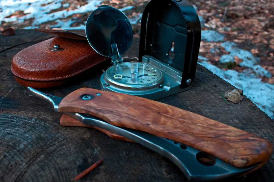 A pocket knife and compass on a piece of wood - the basic tools you need to pack to hike safely, one of the best beginner hiking tips