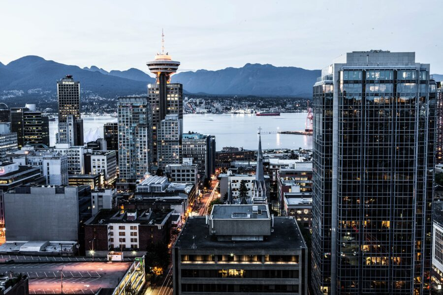 View of the buildings of downtown Vancouver at dusk, and the North Shore Mountains and Pacific Ocean as a backdrop - the last stop on your drive from Calgary to Vancouver
