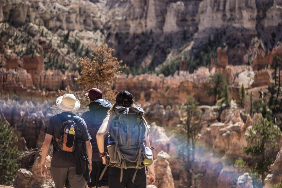 Group of three friends hiking the Grand Canyon together - One of the best safety hiking tips is to hike with others