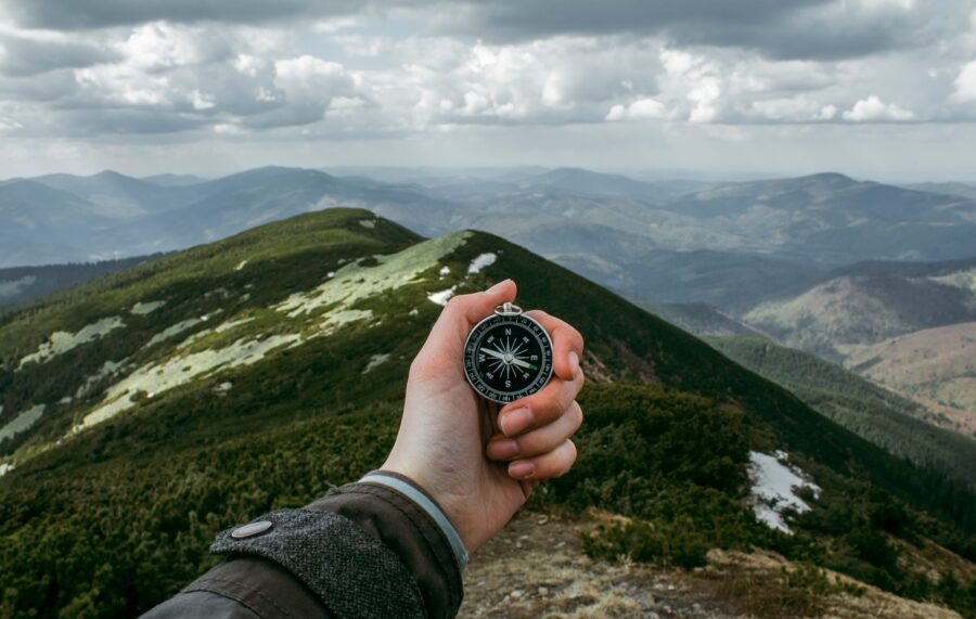 A hand holding out a compass on a hike in the mountains - One of the tips on how to prepare for a hike: bring one of the ten essentials!
