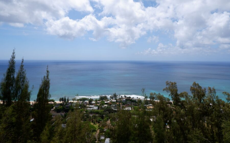 Picture of a viewpoint from one of the best hikes in Oahu - the blue ocean extending to the horizon, and a small neighborhood before the beach - where I went to travel as a college student