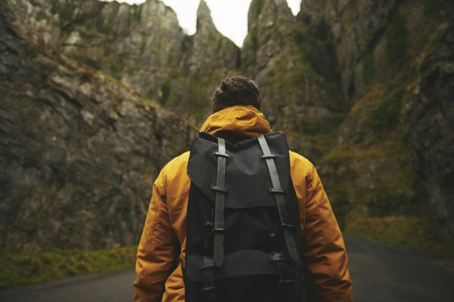 Hiker in the mountains in a yellow jacket carrying a black backpack - Remember to pack light when hiking!