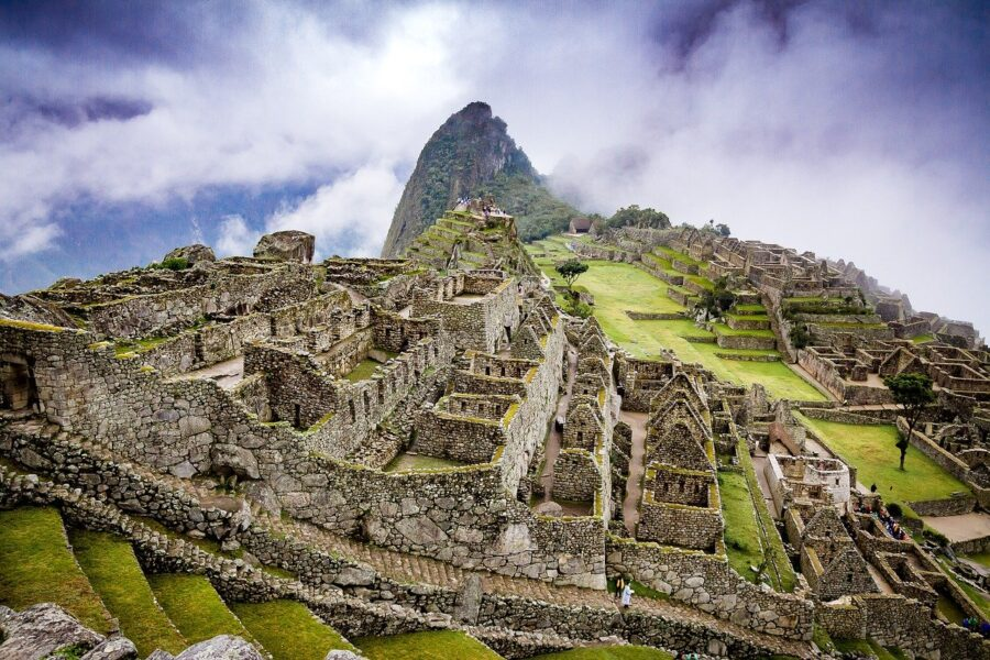 The ruins and mountains of Machu Picchu, Peru surrounded by clouds - One of the best destinations for budget backpackers!