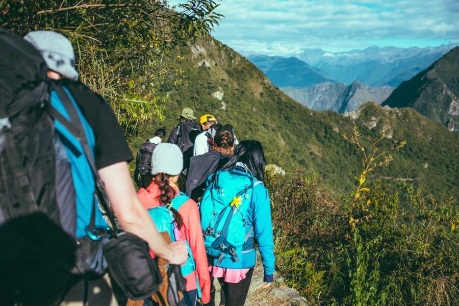 A group of hikers wearing appropriate clothing and backpacks - One of the best hiking tips for beginners is to dress appropriately and in layers!