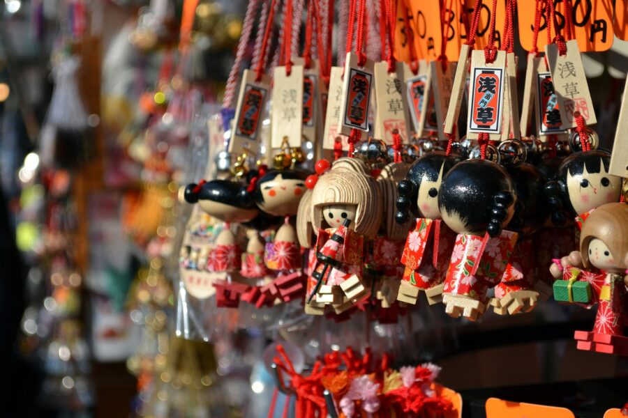 Several small, wooden souvenir keychains at a shop in Tokyo, Japan - a small backpacking cost