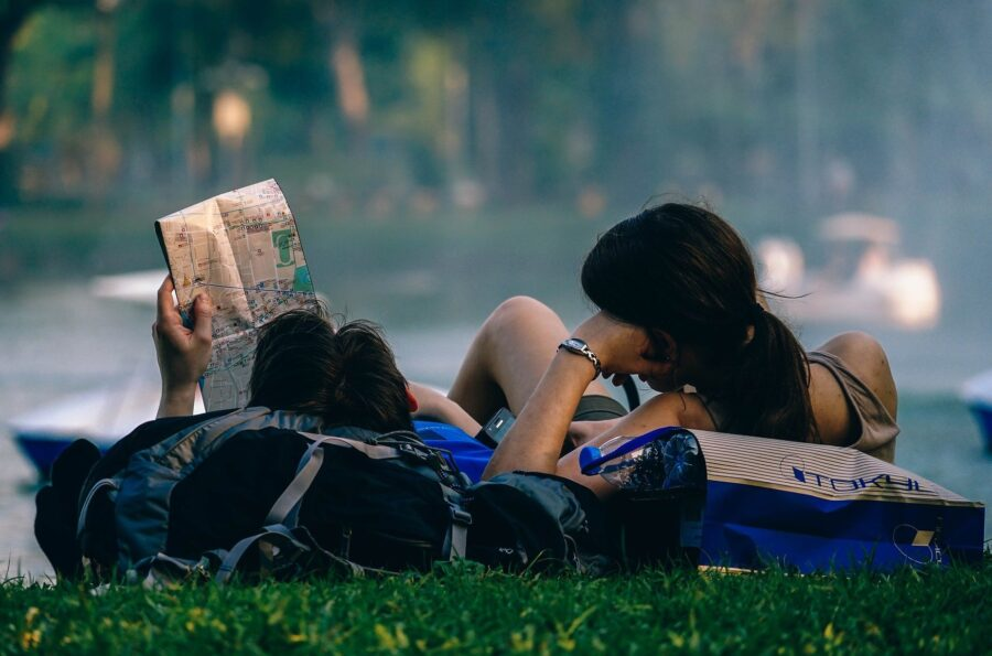 The Best Tips and Tricks to Travel as a Student - Two Students laying on the grass with backpacks and a map