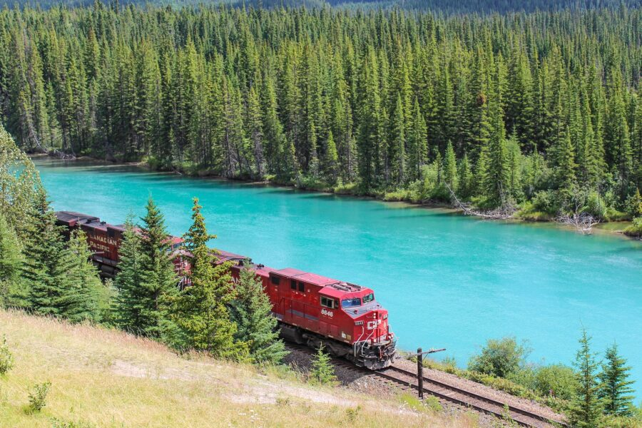 A train from the Canadian Pacific Railway beside a clear blue river near Revelstoke, BC - a sight on the drive from Calgary to Vancouver!