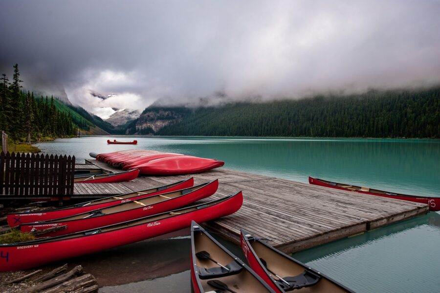 Several canoes docked at the canoe rental spot on the turquoise Lake Louise, an incredible experience on your Calgary to Vancouver road trip