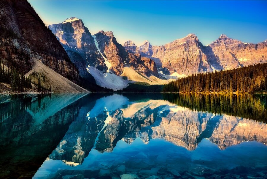 The stunning Canadian Rocky mountains reflected on Moraine Lake, an unmissable stop on your Canadian Rockies Road Trip