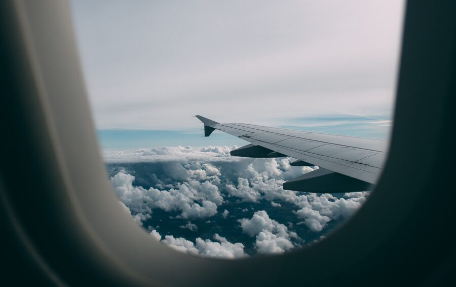 View from the airplane window, of the plane wing and fluffy clouds on an overcast day
