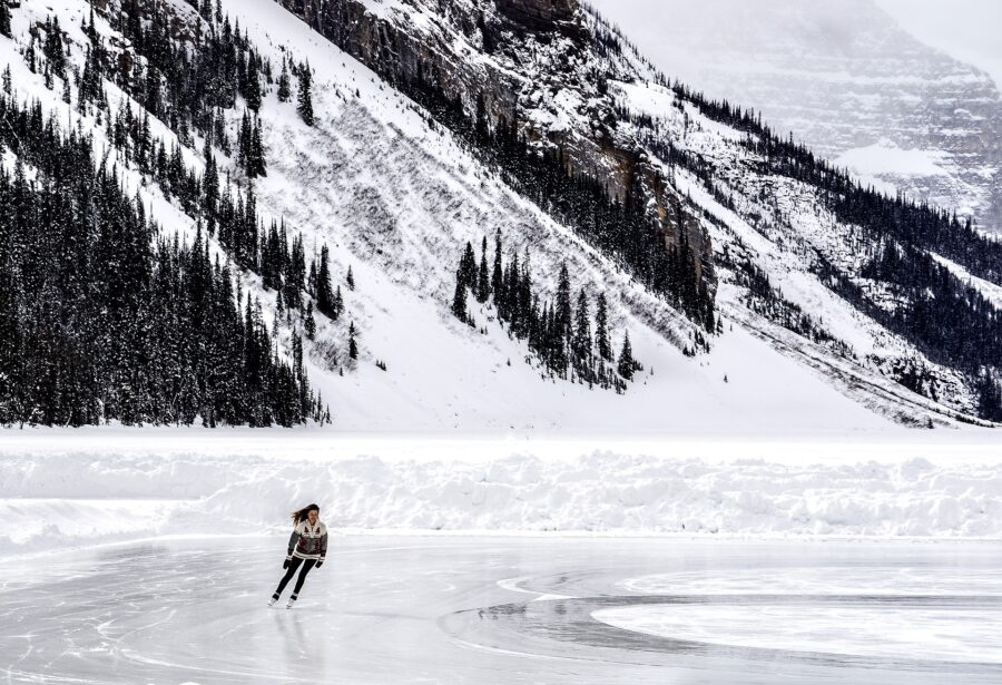 Women in sweater skating on the frozen and snow-covered Lake Louise - The Canadian Rockies in the Winter