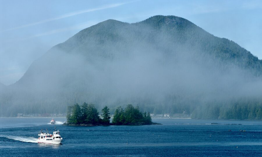 A small white boat passing through the blue Pacific Ocean surrounding the Gulf Islands near Salt Spring Island BC