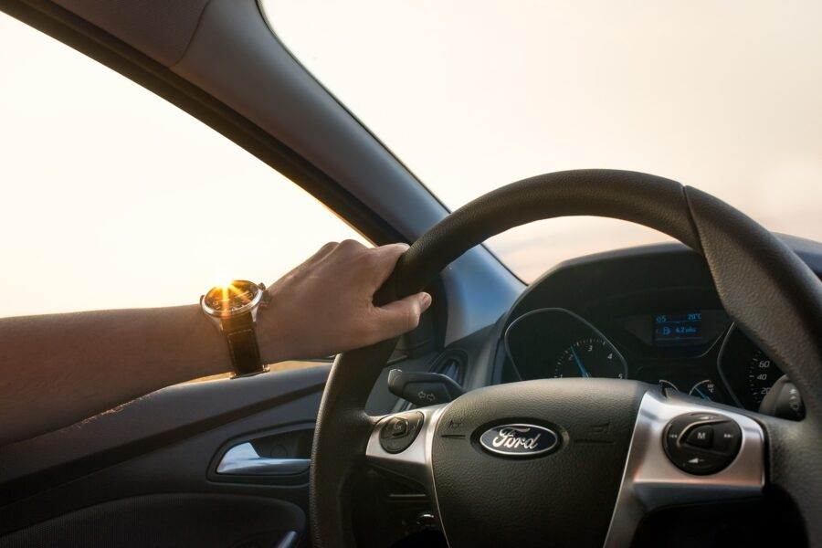 A man's arm holding the steering wheel of a rented Ford car