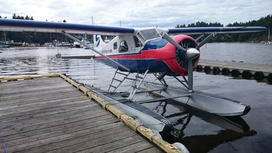 A blue, red, and white Salt Spring Air seaplane stationed at Ganges Harbour, one of the quickest ways to travel from Vancouver to Salt Spring Island