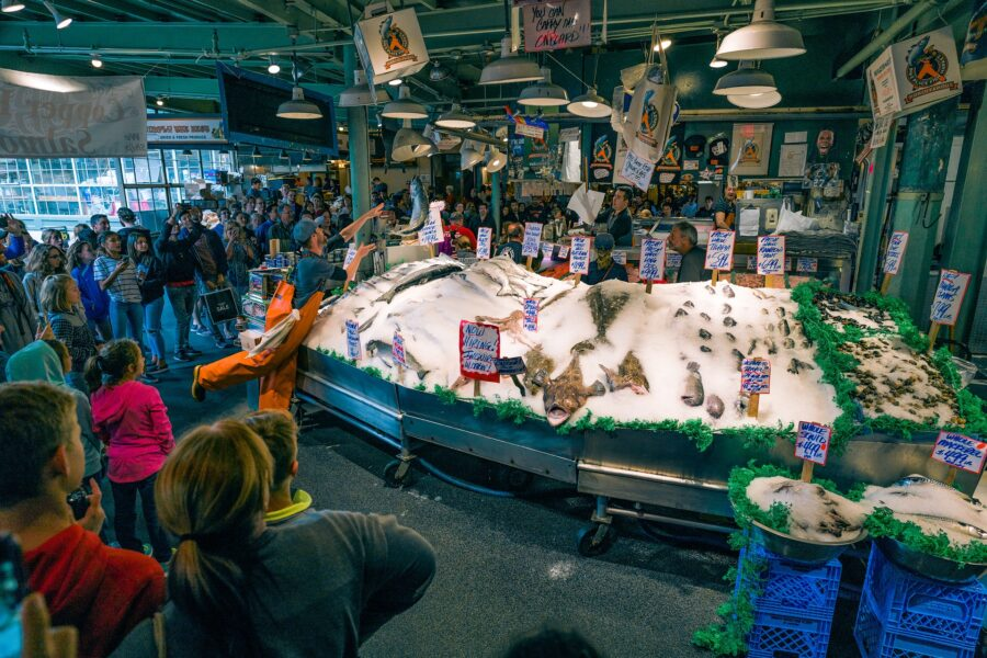 A crowd of people huddled around a fresh fish stand as a fisherman throws fish onto the display of ice at Pike Place Public Market in Seattle